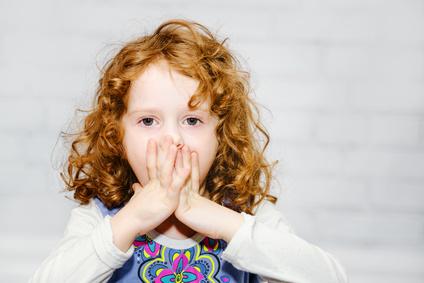 enfant qui met ses mains devant la bouche
